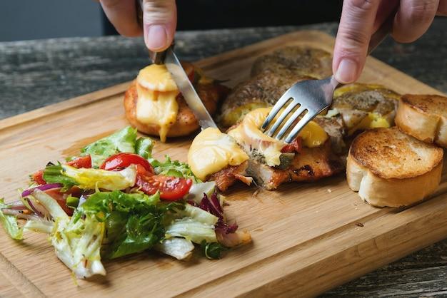 木の板にチーズ、ベイクドポテト、サラダを添えた焼きチキンフィレ。クイックディナー料理のレシピ。健康的な自家製食品。鶏の切り身とのおいしい夕食。