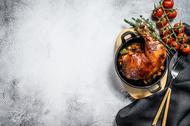 Baked chicken leg with seasonings in a frying pan. gray background