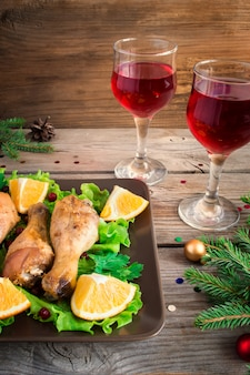 Baked chicken legs on a plate with greens, oranges and cranberries.