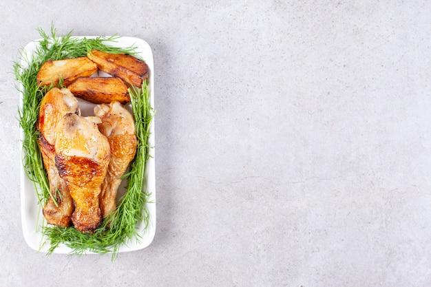 흰색 접시에 채소와 구운 된 닭 다리