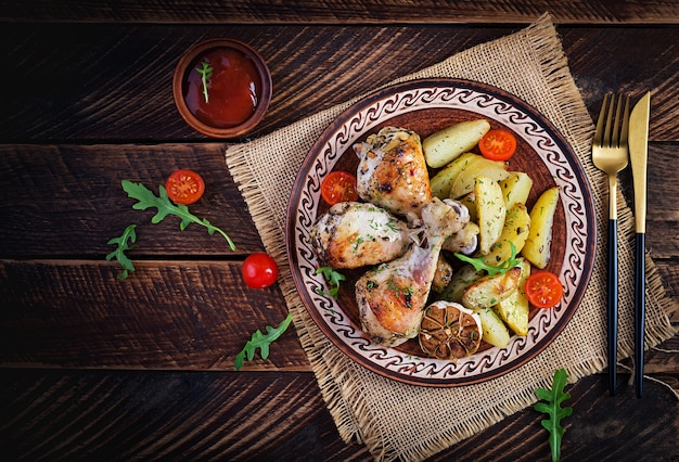 Baked chicken legs with slice potatoes and herbs. barbecue chicken drumsticks on wooden table. top view, overhead, copy space.