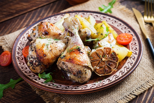 Baked chicken legs with slice potatoes and herbs. barbecue chicken drumsticks on wooden table.