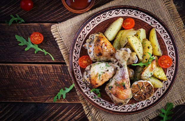 Baked chicken legs with slice potatoes and herbs.
