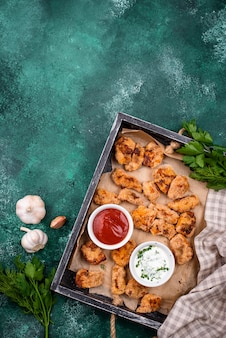 Baked chicken nuggets with sauces on green table