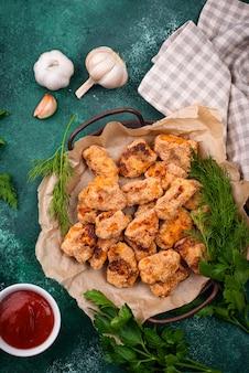Запеченные куриные наггетсы с соусами на зеленом столе