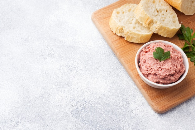 Baked chicken pate in a plate and pieces of bread on the board. copy space.