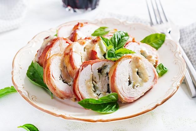 Запеченные куриные рулеты с базиликом и сыром на тарелке. здоровый обед. кето диета.