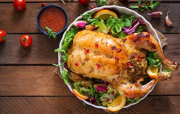 お祝いテーブルでのクリスマスディナーにご飯を詰めた焼きチキン