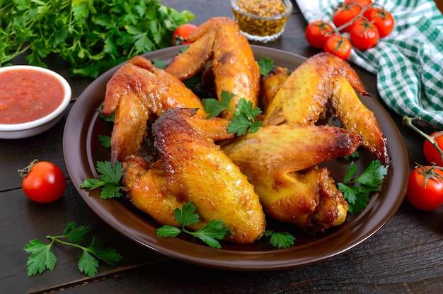 Baked chicken teriyaki wings in honey mustard sauce with adjika and mustard