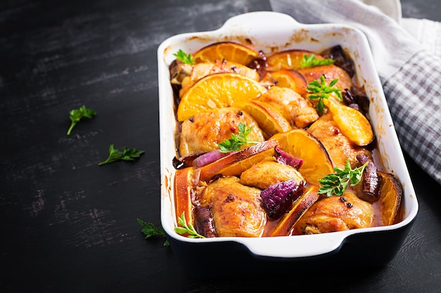 Baked chicken thighs. appetizing slices of baked chicken with red onion and oranges in a baking dish.