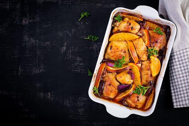 焼きたての鶏の太もも。ベーキング皿に赤玉ねぎとオレンジを入れた焼きチキンの食欲をそそるスライス。