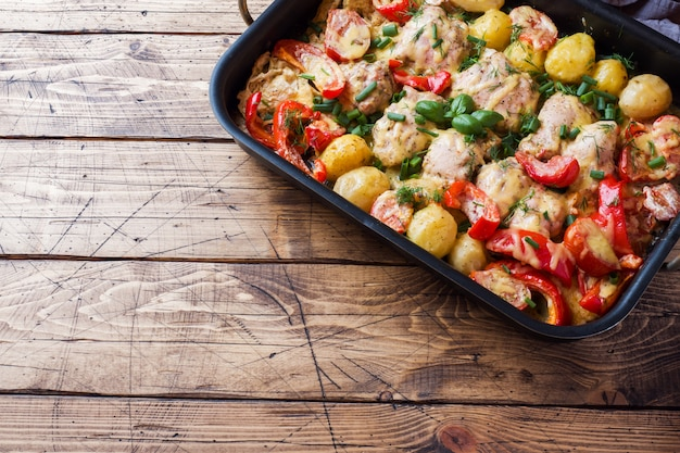 Baked chicken thighs, potatoes and vegetables in a baking tray on a wooden table