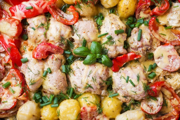 Baked chicken thighs, potatoes and vegetables, close up