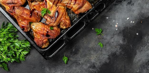 Запеченные куриные крылышки и ножки барбекю на темном каменном столе. формат длинного баннера, вид сверху.