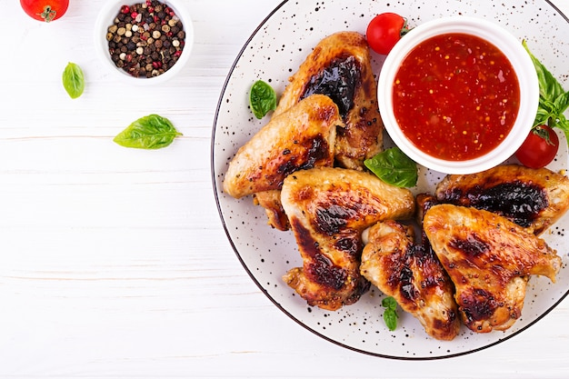 Baked chicken wings in the asian style and tomatoes sauce on plate