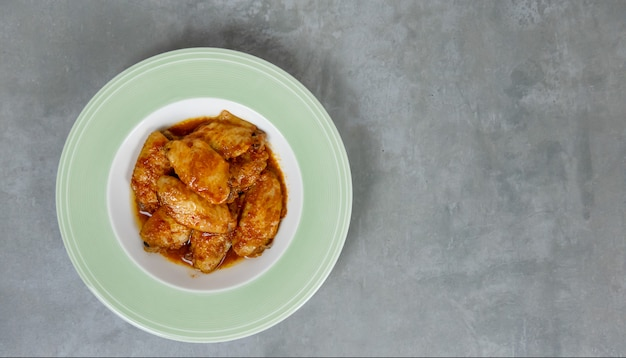 Baked chicken wings on dish over wooden background
