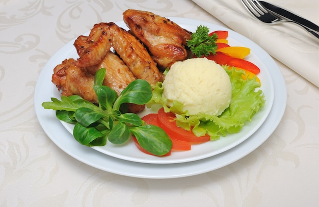 Запеченные куриные крылышки в медово-соевом маринаде с чесноком, картофелем и овощами