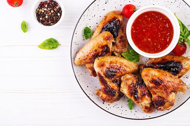 접시에 토마토 소스와 아시아 스타일의 구운 닭 날개