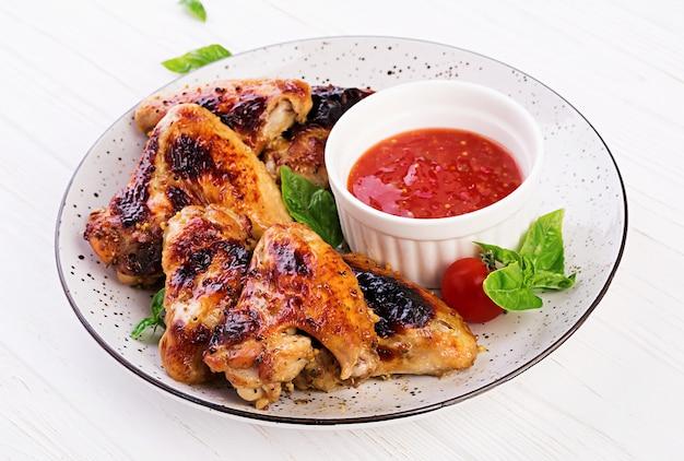 Запеченные куриные крылышки в азиатском стиле и томатный соус на тарелке