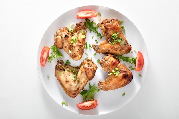 Запеченные куриные крылышки на белом фоне. продукт с высоким содержанием белка и карамелизированных жиров.