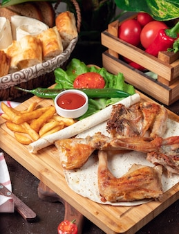 Baked chicken wings with french fries in lavash with vegetables and ketchup on wooden board