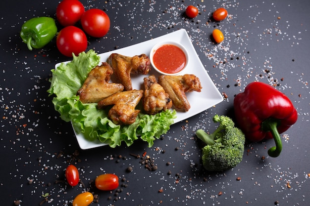 Baked chicken wings with red sauce, on black with tomatoes, red green peppers and broccoli