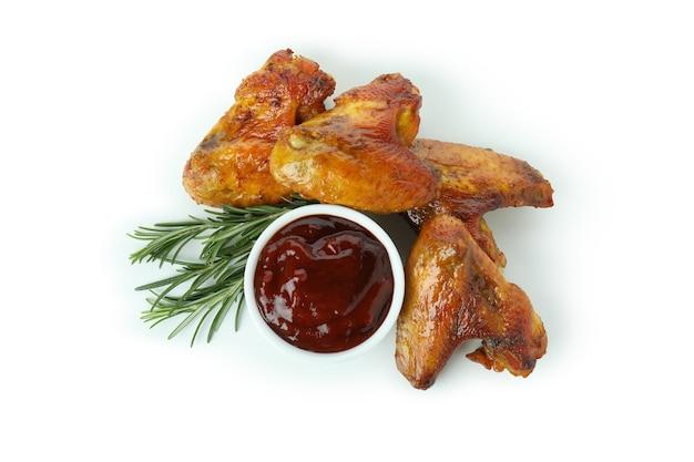 Запеченные куриные крылышки с розмарином и соусом на белом фоне