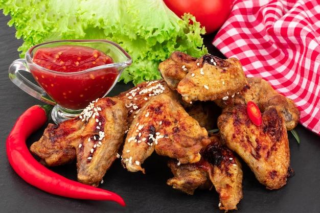 Запеченные куриные крылышки с кунжутом и сладким соусом чили на темной поверхности.