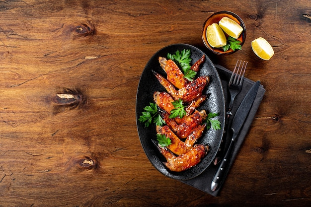 Запеченные куриные крылышки с кунжутом, петрушкой и лимоном на вид сверху черной тарелке.