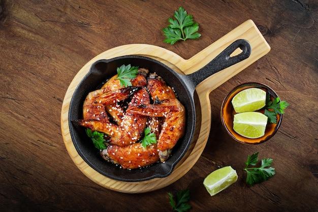 Запеченные куриные крылышки с кунжутом, петрушкой и лаймом на черной сковороде и вид на деревянный стол.