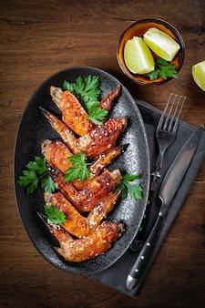 Запеченные куриные крылышки с кунжутом, петрушкой и лаймом на черной тарелке, вид сверху