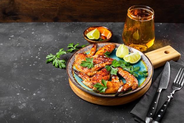 Запеченные куриные крылышки с кунжутом, петрушкой и лаймом на тарелке и бокалом пива на столе