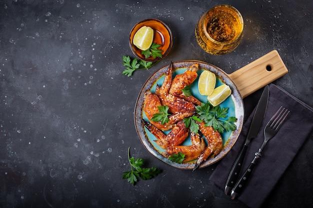 Запеченные куриные крылышки с кунжутом, петрушкой и лаймом на тарелке и стакане пива