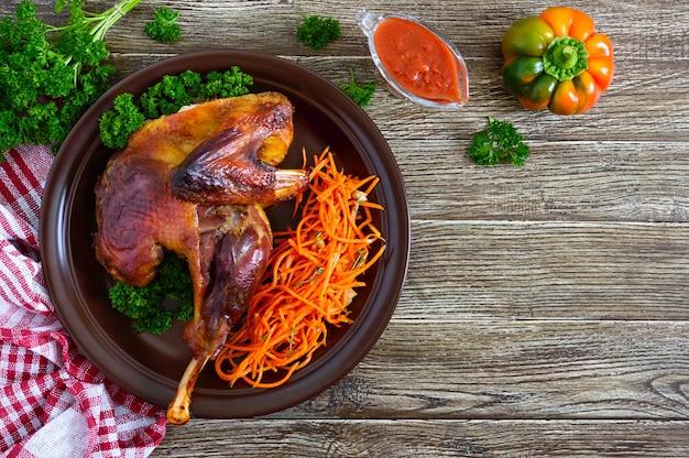 Запеченный цыпленок с золотистой хрустящей корочкой и салатом из свежей моркови на керамической тарелке. вид сверху. плоская планировка