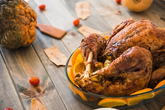 Baked chicken with green pumpkin on table