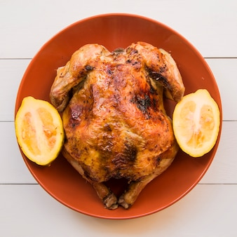 Baked chicken with lemon on plate