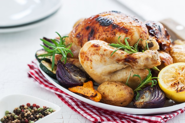 Baked chicken with lemon and vegetables in a dish
