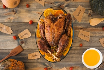 Baked chicken with oranges on wooden table