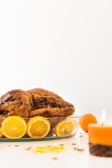 Baked chicken with oranges on white table