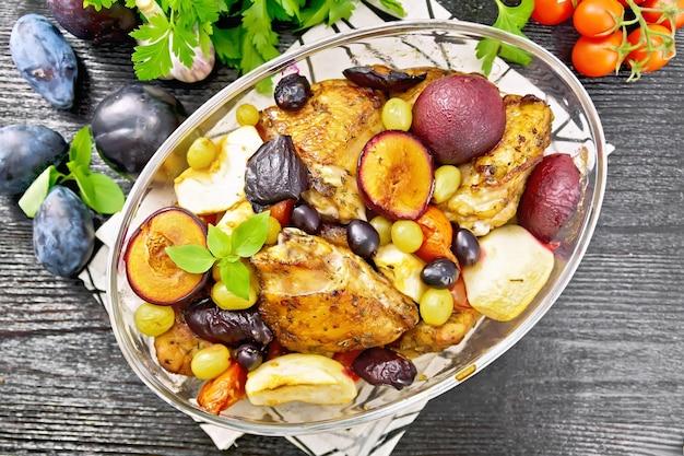Запеченный цыпленок с помидорами, яблоками, сливами и виноградом в стеклянной жаровне на салфетке, чеснок, петрушка и базилик на фоне деревянной доски сверху