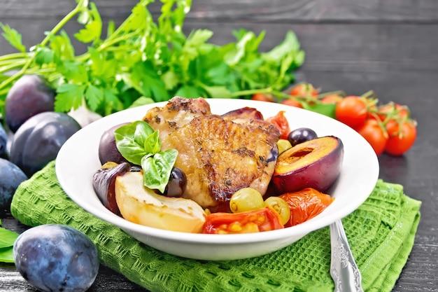 緑のナプキン、ニンニク、パセリ、木の板の背景にバジルのプレートにトマト、リンゴ、プラム、ブドウと焼き鶏