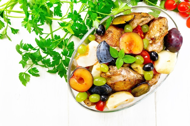 Baked chicken with tomatoes, apples, plums and grapes in a glass roaster on a kitchen towel, garlic, parsley and basil on background of light wooden board from above