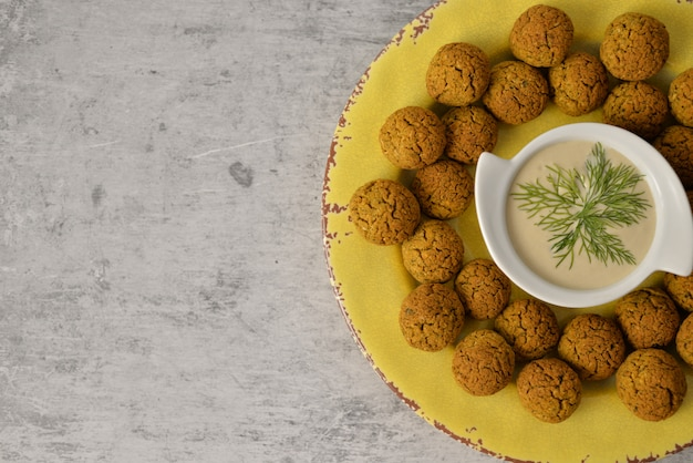Baked chickpea falafel balls on yellow plate on grey , healthy and vegan food with tahini deep , traditional mediterranean , top view , flat lay with copy space