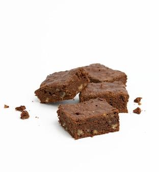 Запеченные кусочки шоколадного брауни с грецким орехом на белом фоне, вкусный десерт