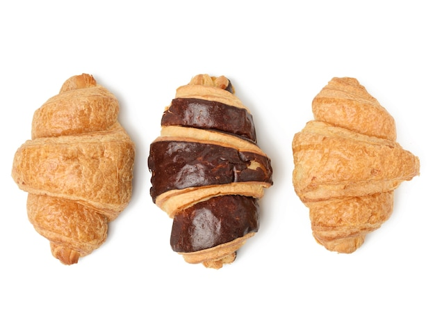 白い表面に分離された白い小麦粉から作られた焼きチョコレートクロワッサン、上面図