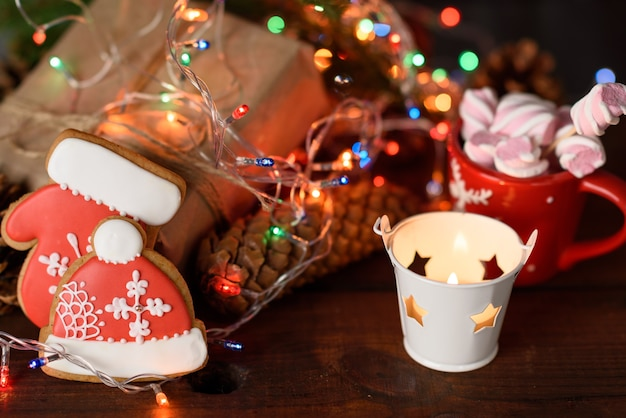 Baked christmas gingerbread cookies, cocoa with marshmallows and burning holiday lights on a brown table