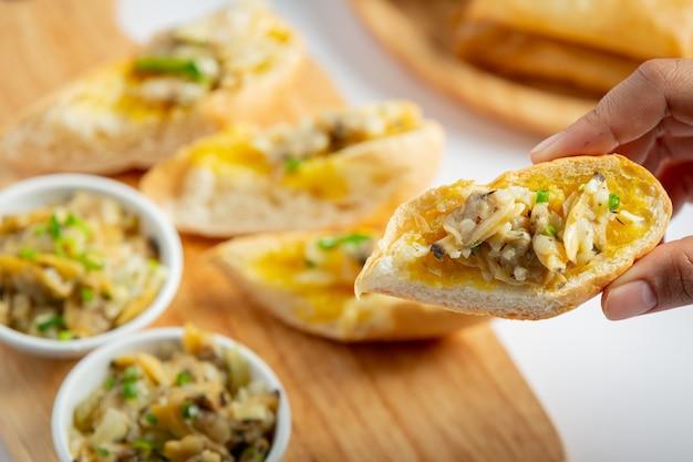 Vongole al forno con aglio e burro servite con pane all'aglio su fondo marmorizzato