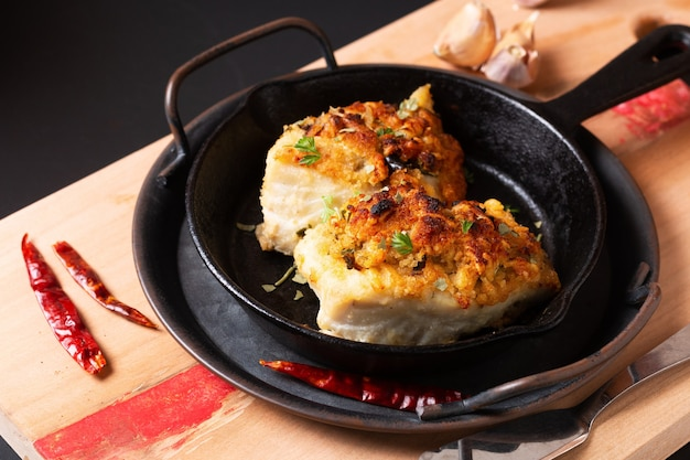 Baked cod fish in skillet iron cast pan