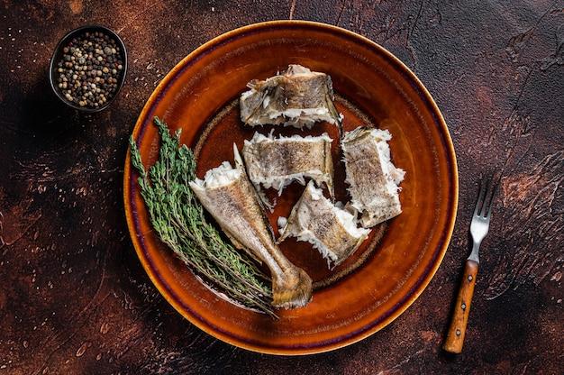 Запеченная треска белая рыба в тарелке. темный деревянный фон. вид сверху.