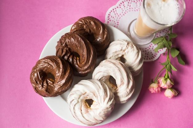 ピンクの背景に焼きたてのクッキーチョコレートドーナツ